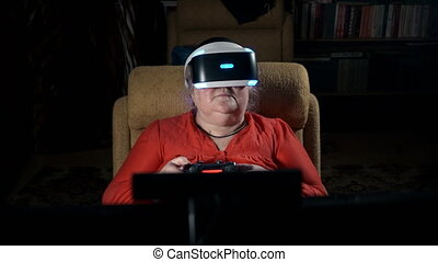 70 year old woman playing video game uses VR headset and gaming controller