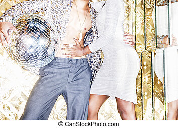 70s disco style couple posing with mirror ball
