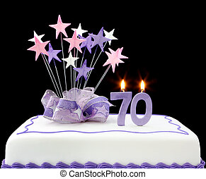 Fancy cake with number 70 candles. Decorated with ribbons and star-shapes, in pastel tones on black background.