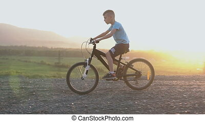 8-9 year boy in blue T-shirt who rides a black bike in a...