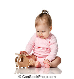 8 month infant child baby girl toddler sitting in pink shirt play with wooden toy isolated on a white