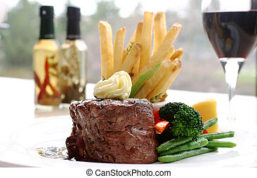 8 oz Tenderloin Steak topped with truffle butter. Served with broccoli, beans, horseradish and fries. Backdrop of a glass of red wine. Shallow DOF.