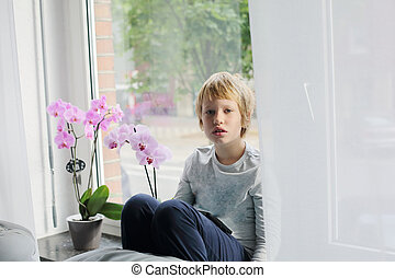 8 year old boy sitting near the window and playing with...