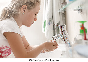 8 year old girl washes her face in the bathroom in the morning