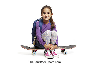 8 year old school girl with backpack sitting on a skateboard...