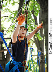 8 years old girl in forest adventure park. Child climb on high rope trail. Outdoor playground with rope way