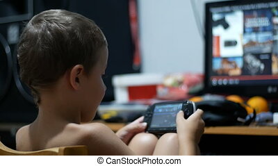 8 Years Old Kid Playing Video Games on a Portable Game...