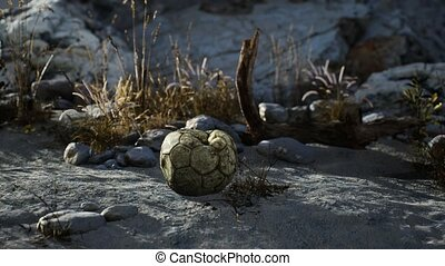 8K old torn soccer ball thrown lies on sand of sea beach
