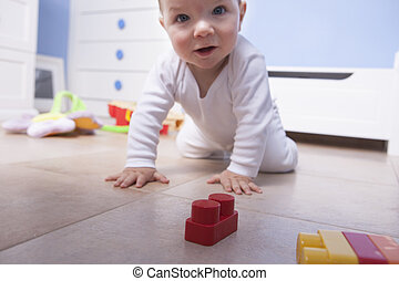 baby boy playing with plastic building blocks