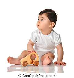 9 month infant child baby girl toddler sitting in white shirt with wood car toy