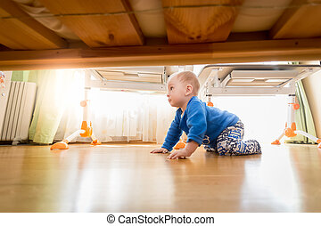 9 months old baby crawling on wooden floor at bedroom
