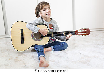9 year old girl learning to play the guitar. Horizontal shot...