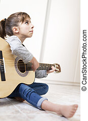 9 year old girl learning to play the guitar. Vertical shot...