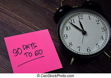 90 Days To Go write on sticky note isolated on wooden table.