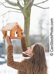 añadir, mujer, joven, alimentador, pájaro, comida, feliz