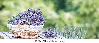 a, バスケット, 満たされた, ∥で∥, 紫色の花, 立つ, 上に, a, 木製のテーブル, 上に, a, 背景, の, 緑, ラベンダー, fields.