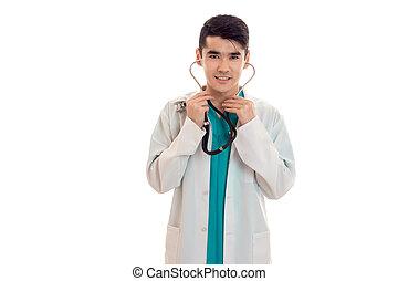 a, 年輕的醫生, 在, a, 白色的實驗室外套, 聽診器, 進, 他的, 耳朵, 以及, 微笑, 被隔离, 在懷特上, 背景