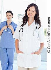 a, 微笑, 護士, 站立, 直立, 當時, 她, 同事, 是, 後面, 她