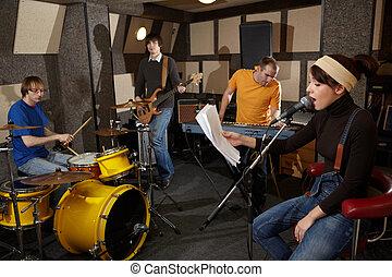 a, 搖滾樂隊, 是, 工作, 在, studio., 聲樂家, 女孩, 是, 唱, 由于, 正文, ......的, 歌, 在, the, 她, 手