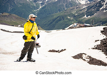 a, 登山家, 中に, a, 帽子, ∥で∥, ガラス, そして, ∥, 氷 一突き, 立つ, 上に, a, 背景, の, a, 雪をいただいた山地