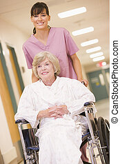 a, 看護婦, 押す, a, 年長の 女性, 中に, a, 車椅子, 下方に, a, 病院廊下