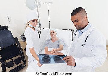 a, 護士, 以及, a, 醫生, 是, 站立, 在旁邊, a, 病人, 由于, cancer., 博士, 是, 藏品, 她, x-ray.