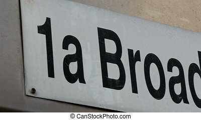 A 1a Broadway sign from the wall. It is in white board with...