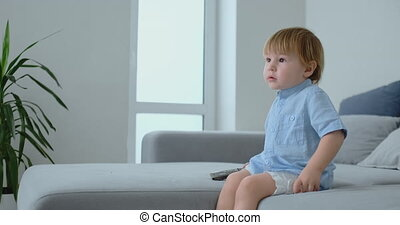 A 2 years old boy sits on a sofa and watches TV sitting with a remote control in his hands.