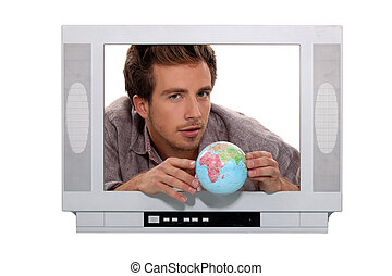a 25 years old man behind a television screen is taking a little globe