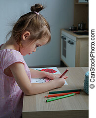 A 4-5 year old girl is engaged in drawing with colored pencils in her room at home