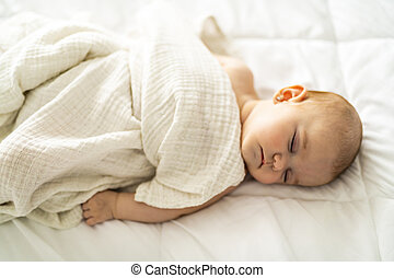 A 4 month baby sleeping on a white bed at home