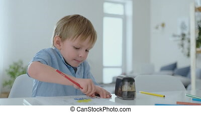 A 4 years old boy sits at home at the table in the living...