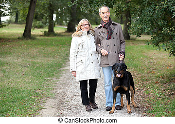 a 60 years old woman holding husband's arm in a park in autumn,  the man is keeping a dog on the leash