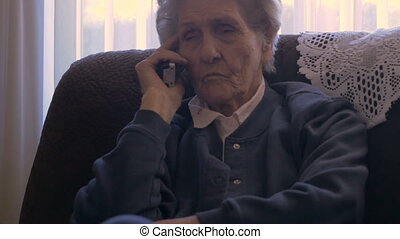 A 90 year old woman on a phone at her home while rubbing her...