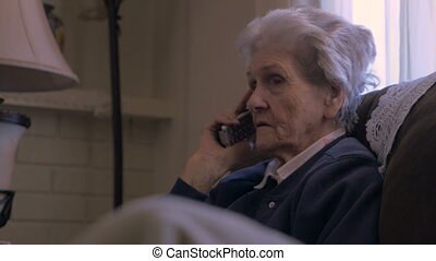 A 90 year old woman talking and listening on a cordless land...