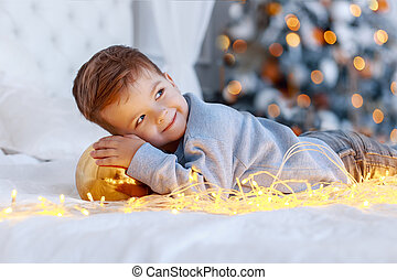 A a cute little boy with a christmass toy ball in front of the christmas tree on the bed. love, happiness concept