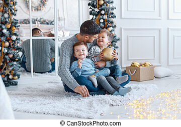 A a daddy with his two sons twins in front of the christmas tree hugging and having fun. big family concept