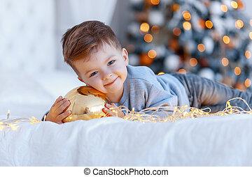 a, a, reizend, kleiner junge, mit, a, christmass, spielzeug, kugel, vor, der, weihnachtsbaum, auf, der, bed., liebe, glück, begriff