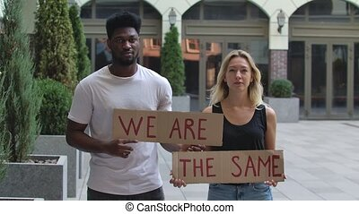 A black man and a white woman stand on the street holding posters for WE ARE and THE SAME. A protest against racism and violence. Stop racism and unity concept. Slow motion. Close up outdoors portrait.