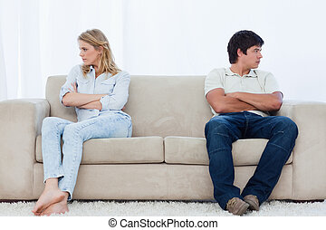 A angry couple sit at the two ends of the couch with their...