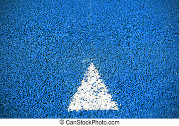 a arrow sign on blue running track