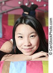 Asian American teen lay on his bedroom