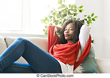Attractive black young woman relaxing on a sofa at home