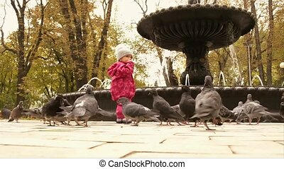 a baby and pigeons in the park
