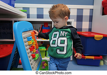 A baby boy playing with plastic blocks