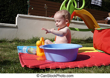 A baby boy playing with water