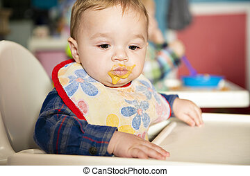 A baby child eats food at the nursery