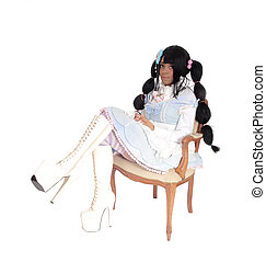 A baby doll woman sitting in armchair.