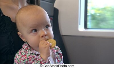 A Baby Eating a Biscuit on the Train - A baby girl eating a...
