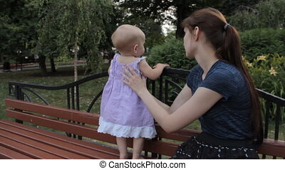 A baby girl climbing on the bench back with her legs, a girl holding her by the buttocks and arm pit.